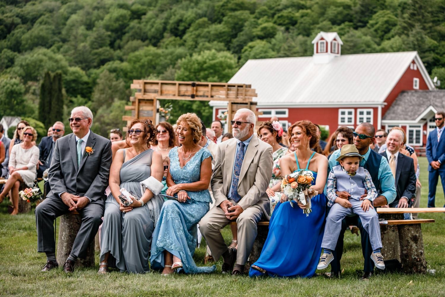 guests watch vermont wedding ceremony from benches with smiles and laughs