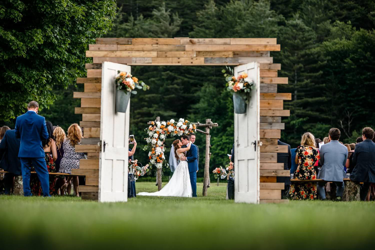 vermont wedding photographer captures bride and groom kissing through ceremony doorway at riverside farm