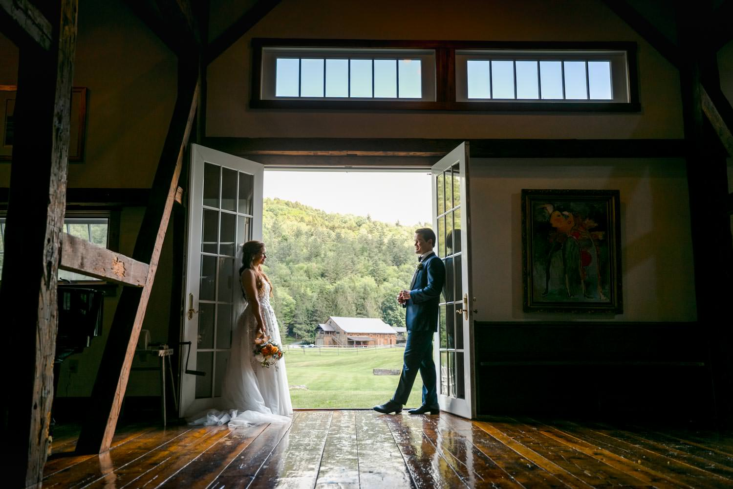 wedding couple poses for photographer in barn doorway at riverside farm vermont