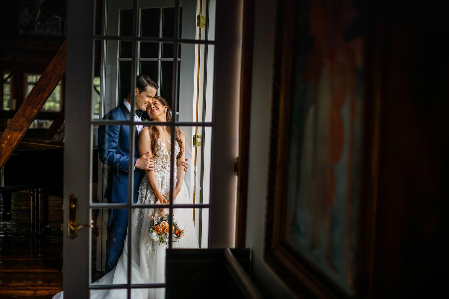 full length photograph of wedding couple embracing behind glass door