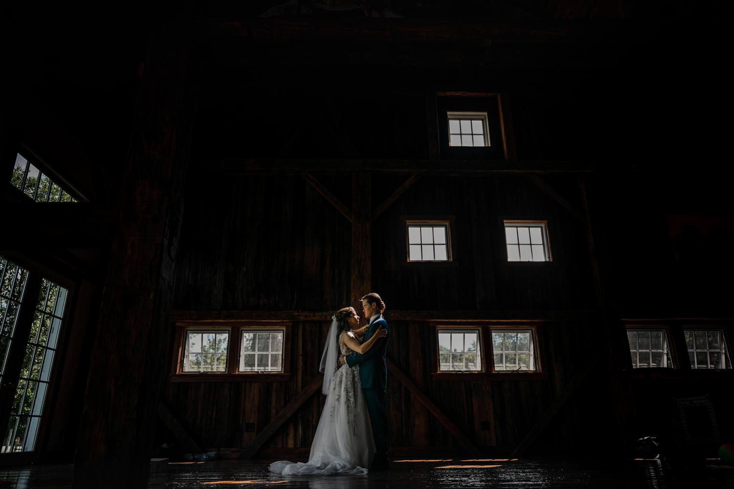 wedding couple look at each other for photographer in riverside farm barn with a series of small windows in the background lighting the vermont scene