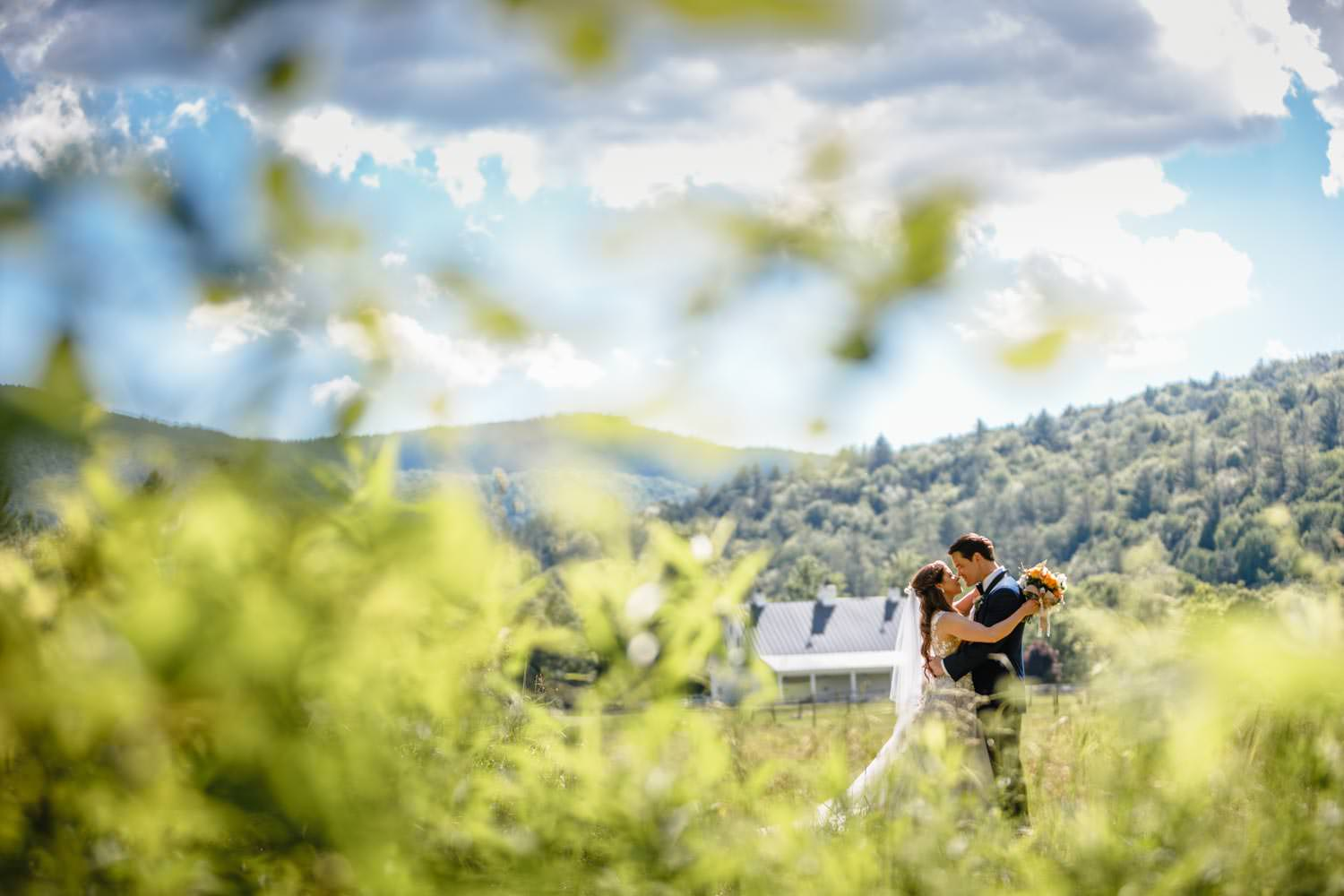 bride and groom in back field of riverside farm in pittsfield vermont while photographer shoots from behind long foreground grass