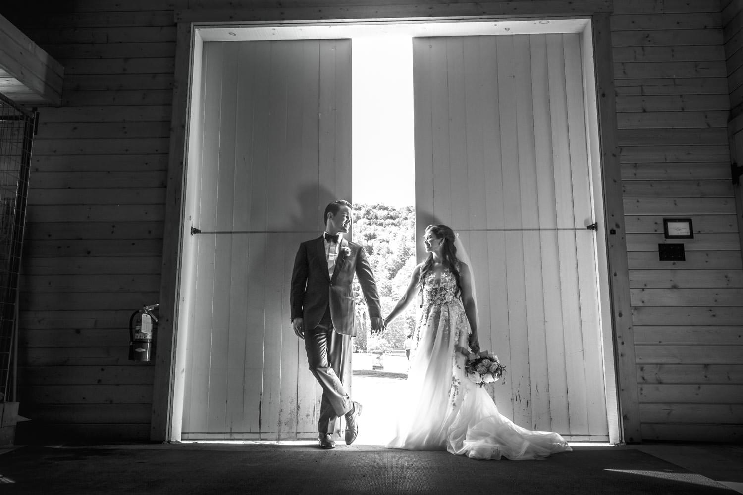 bride and groom pose for vermont wedding photographer in barn doorway
