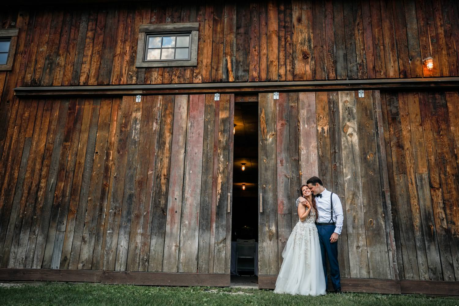 vermont wedding couple embraces in front of riverside farm reception barn