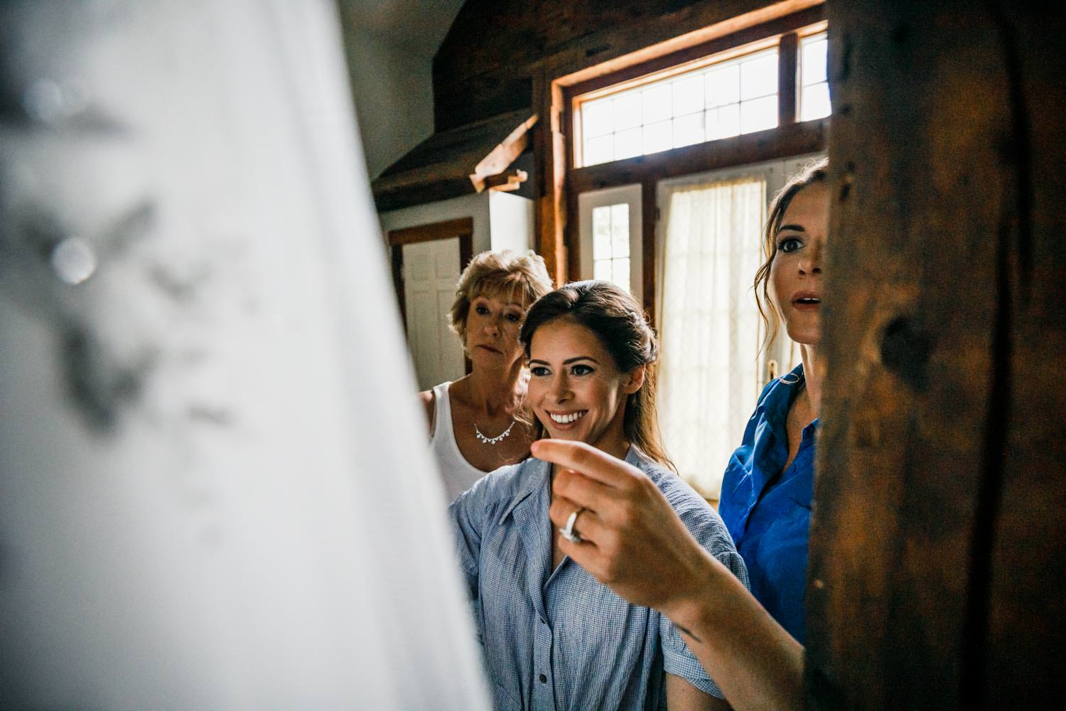 bride examines dress with vermont wedding photographer in bridal suite at riverside farm