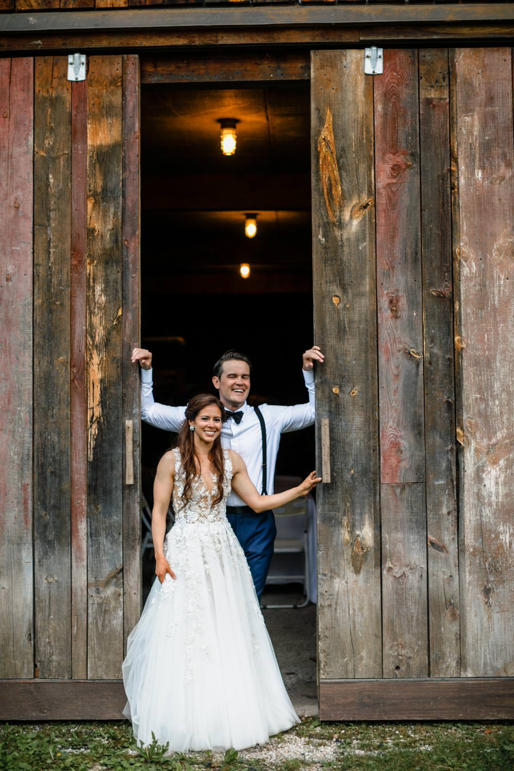 bride and groom pose for vermont wedding photographer in reception barn doorway