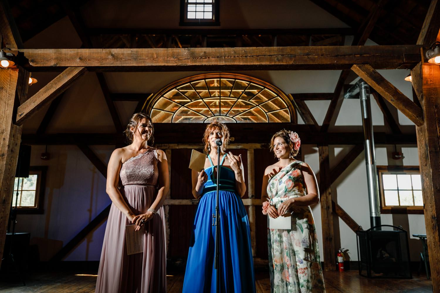 wedding maids of honor give speech in reception barn at riverside farm vermont