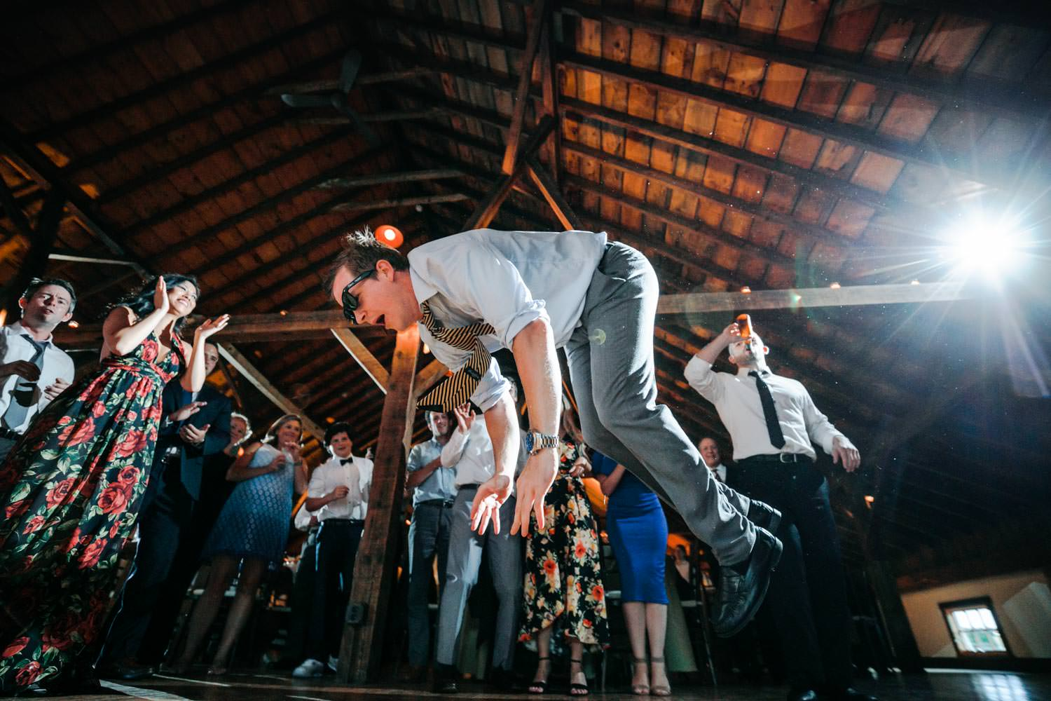 vermont wedding guest dances with full body horizontal in the air, lucky photographer captures the moment