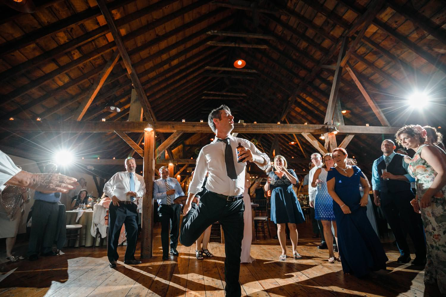 wedding guest performs one-legged chicken dance while vermont wedding photographer lights background with starburst flashes