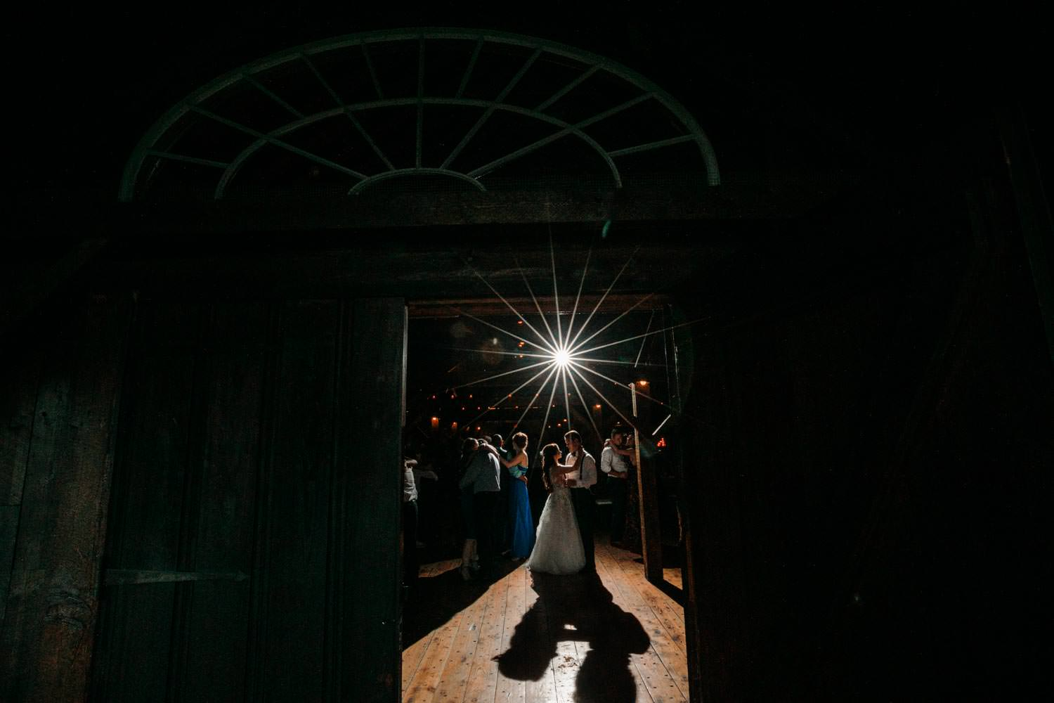 bride and groom dance at their riverside farm vermont wedding reception, photographer shoots them though barn door way with starburst flash in background