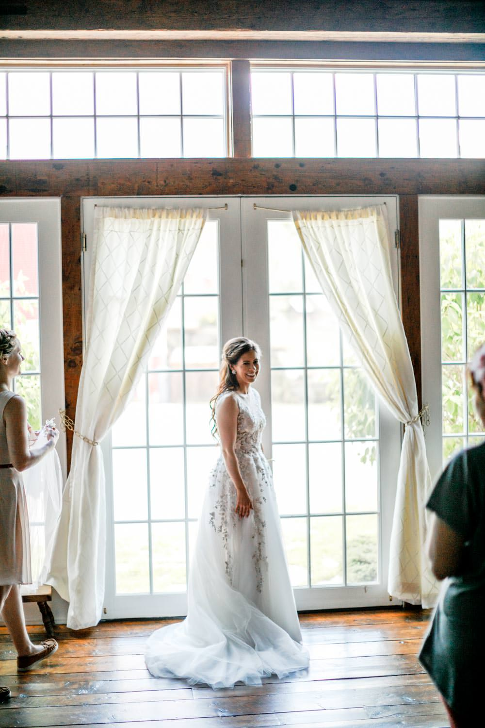 bride stands at glass doorway for photographer in riverside farm wedding suite pittsfield vermont