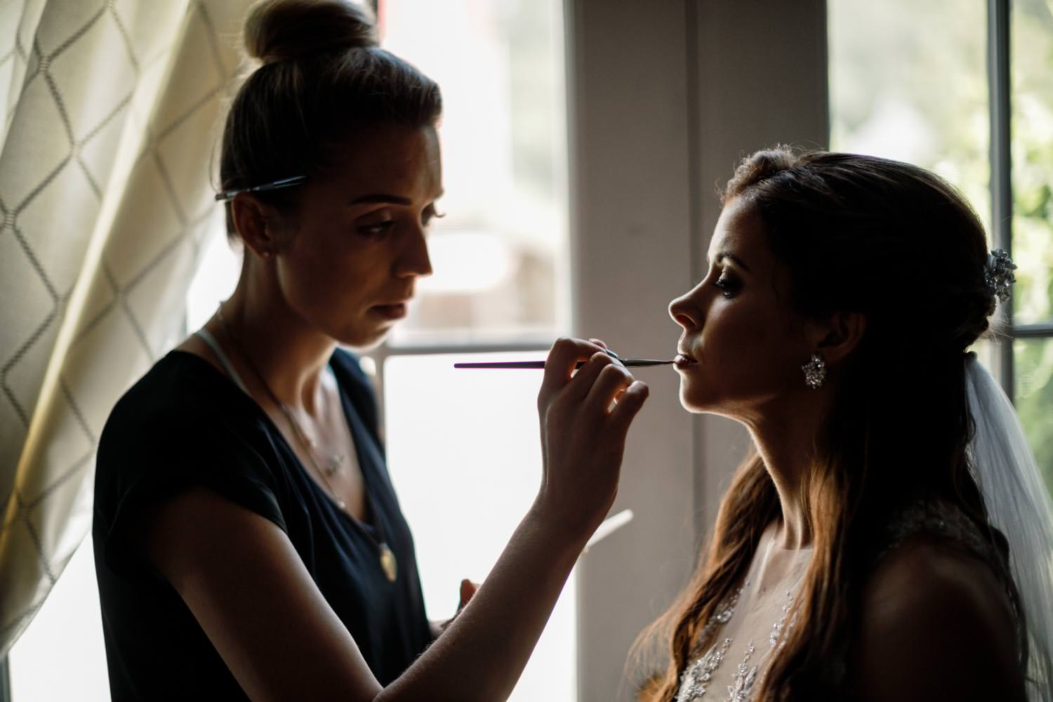 bride gets lips touched-up by makeup artist in riverside farm wedding suite pittsfield vermont