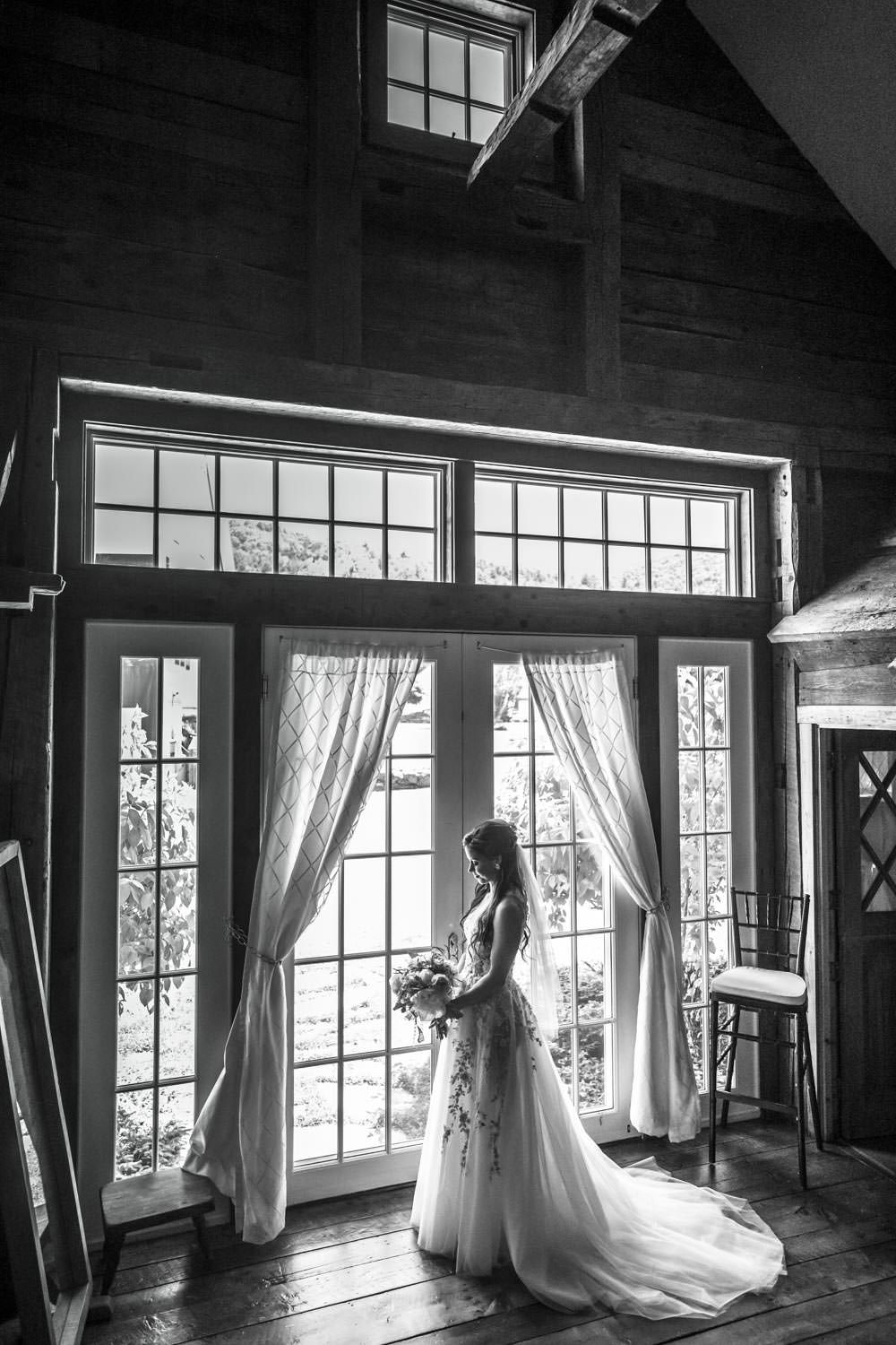 black and white photographer of bride doorway of riverside farm wedding suite pittsfield vermont