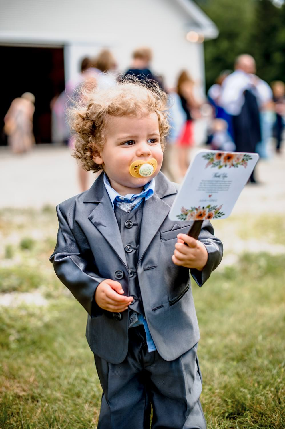child wedding guest holds a program at riverside farm wedding pittsfield vermont