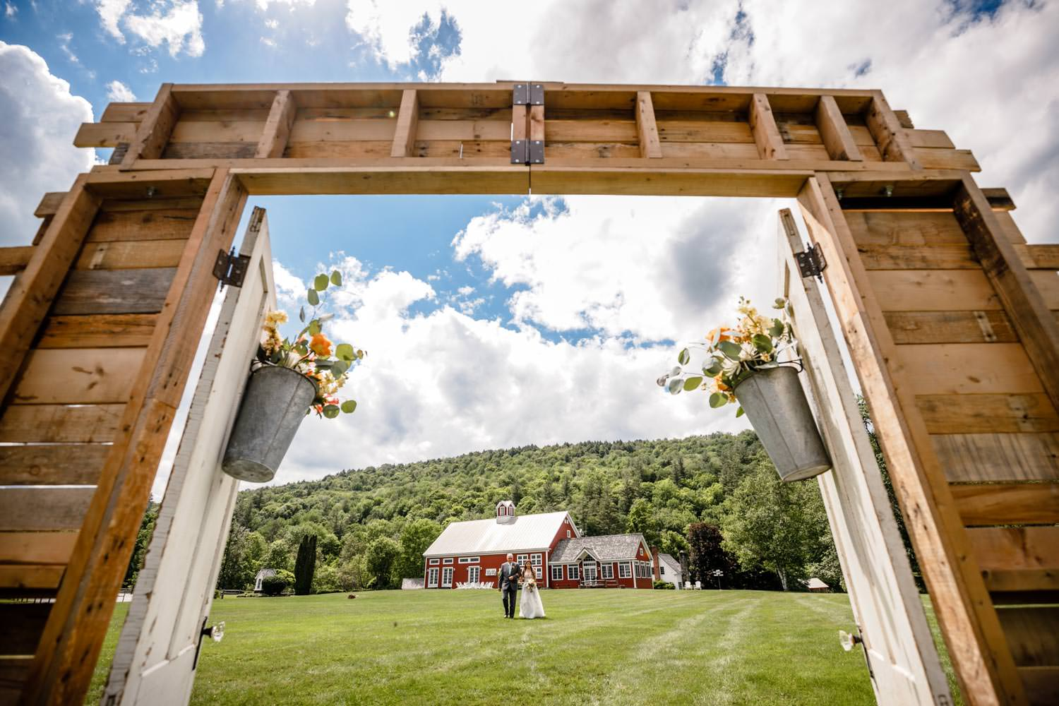 bride and father approach wedding photographer through a ceremony doorway at riverside farm vermont