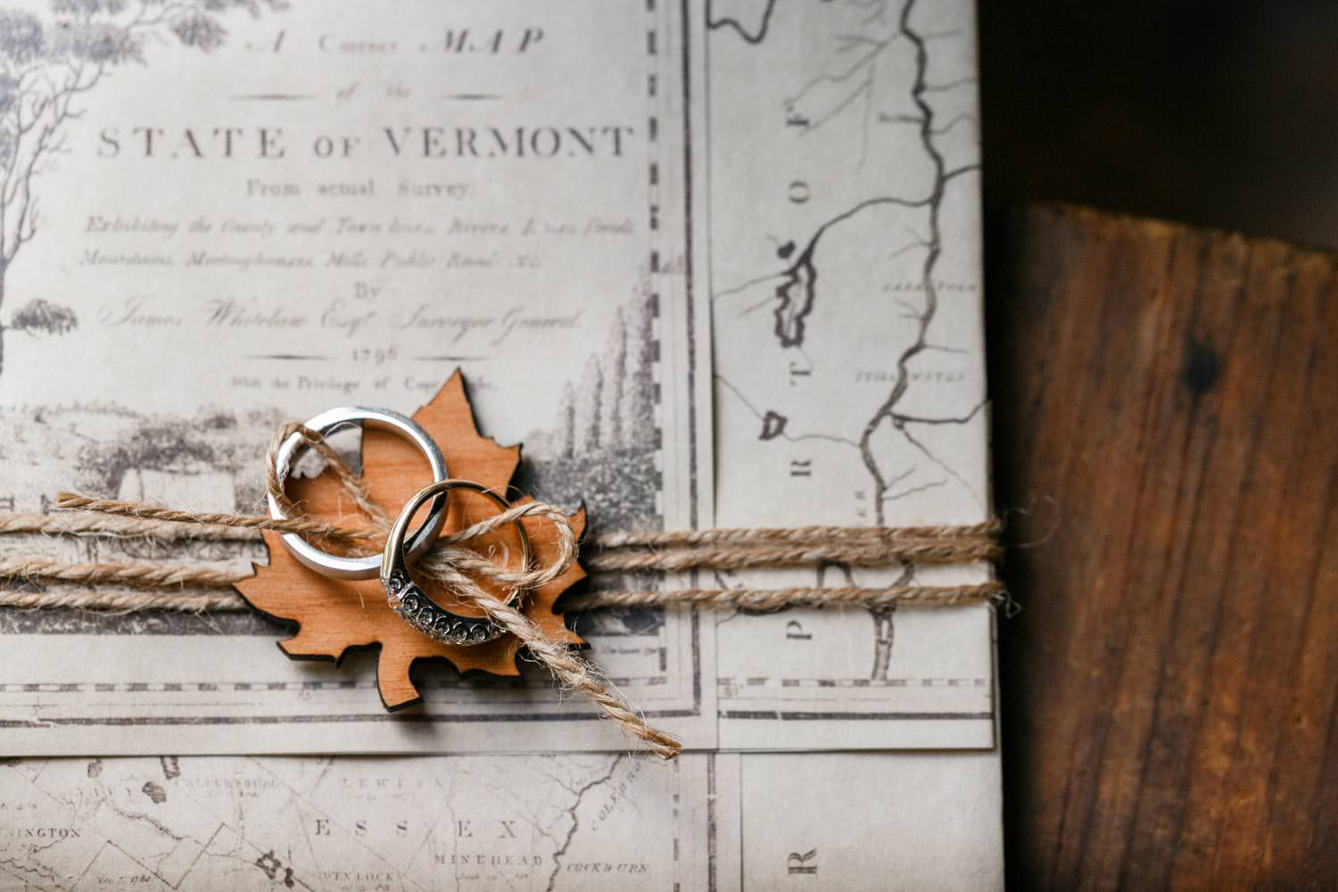 vermont wedding photographer composes riverside farm couple's ring on wedding invite