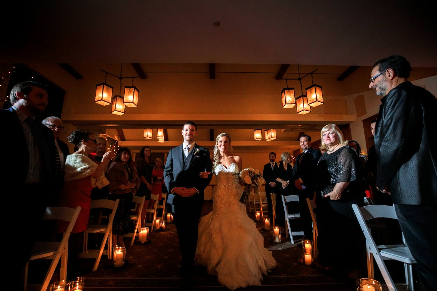 bride walks down aisle towards Stowe Mountain Lodge wedding photographer sitting at a low angle