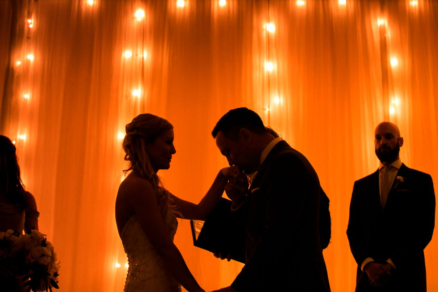 groom kisses brides hand at Stowe Mountain Lodge wedding ceremony