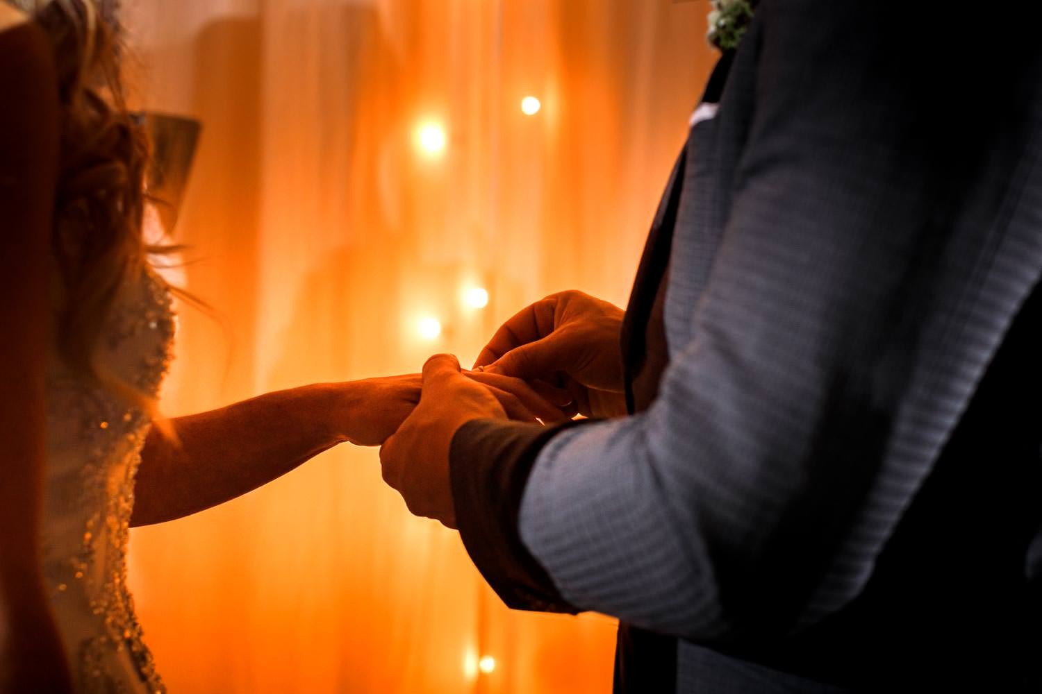 groom places ring on hand during wedding ceremony
