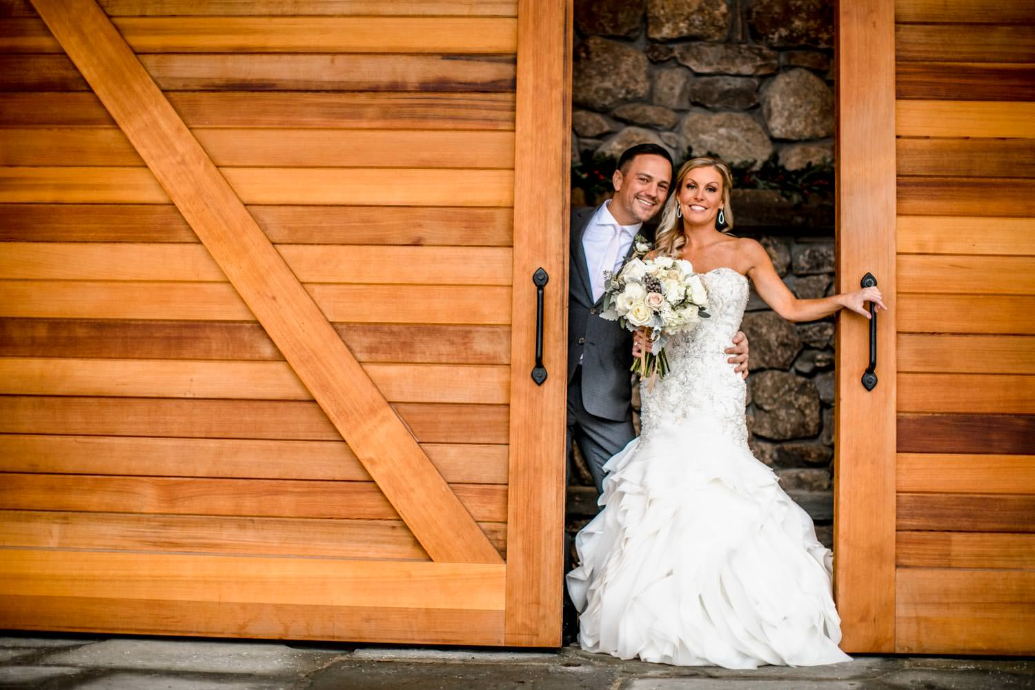 bride and groom pose for wedding photographer in doorway by ice rink at Stowe Mountain Lodge