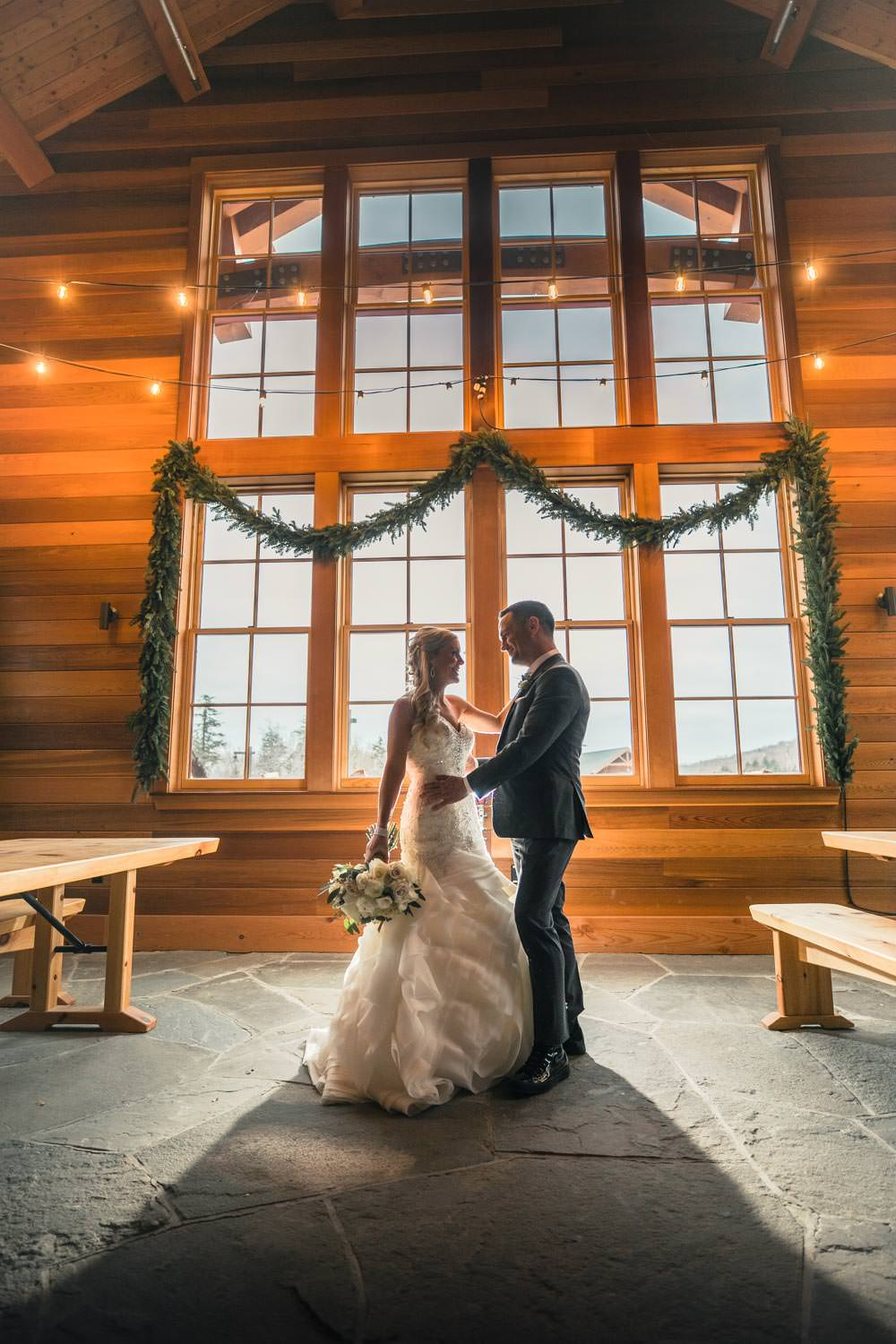 bride and groom stand face to face after their wedding in warming lodge at Stowe Mountain resort