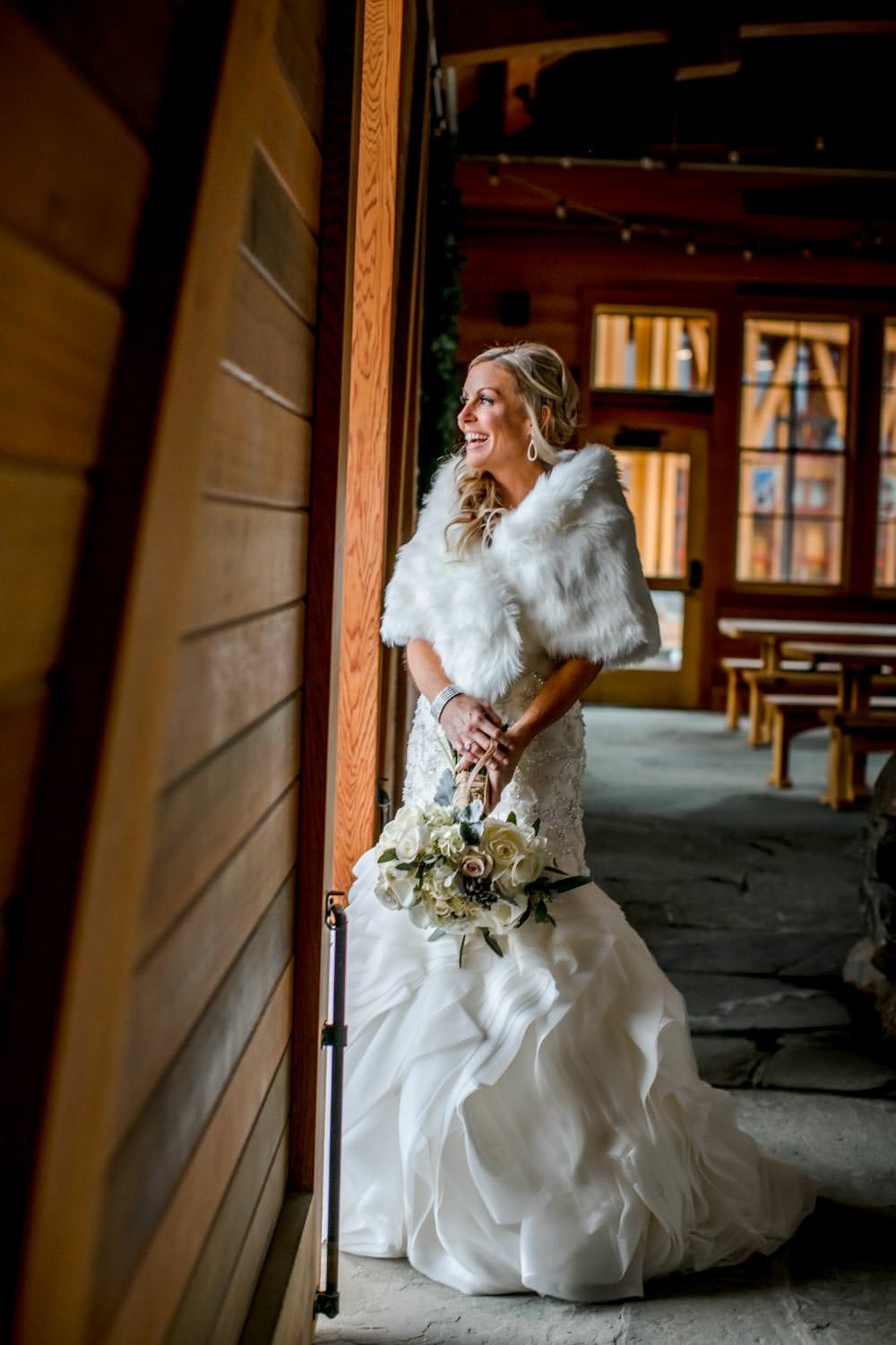 bride stands in doorway of warming lodge at Stowe Mountain resort after her wedding
