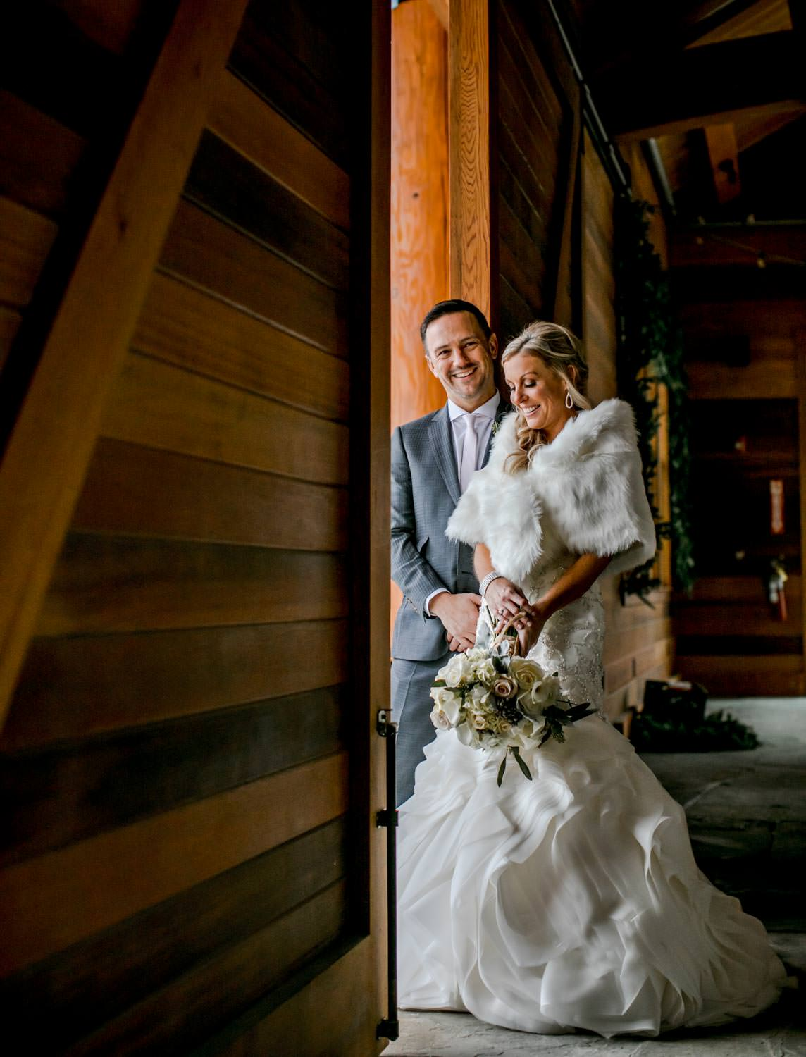 bride and groom stand in doorway of warming lodge at Stowe Mountain resort for wedding portraits