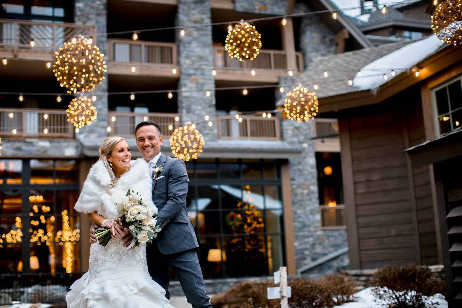 bride and groom standing outside of lodge at Stowe Mountain resort for wedding photographer with winter holiday lights in the background