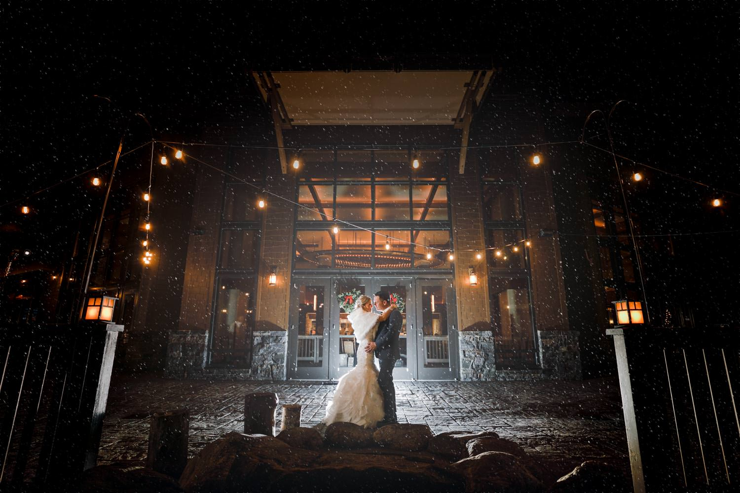 bride and groom standing in front of lodge for night photography at Stowe Mountain resort with winter holiday lights and fire pit