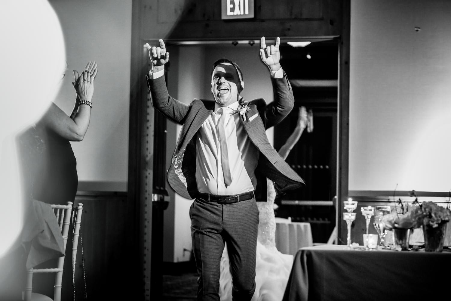 Groom enters ballroom at Stowe Mountain Lodge for wedding introductions with devil horn hand gesture towards the photographer