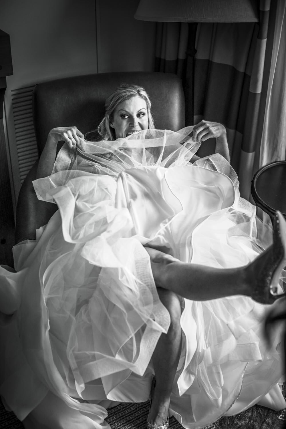 bride sits in chair and kicks up heals for photographer in bridal suite for her stowe mountain odge wedding in vt