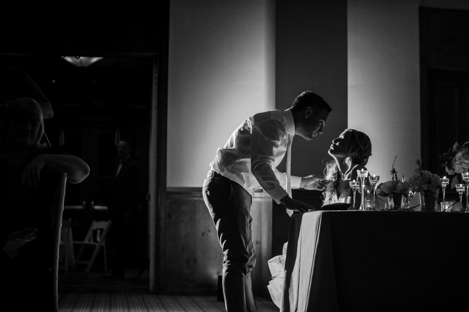 groom kissing bride at table after their wedding first dance