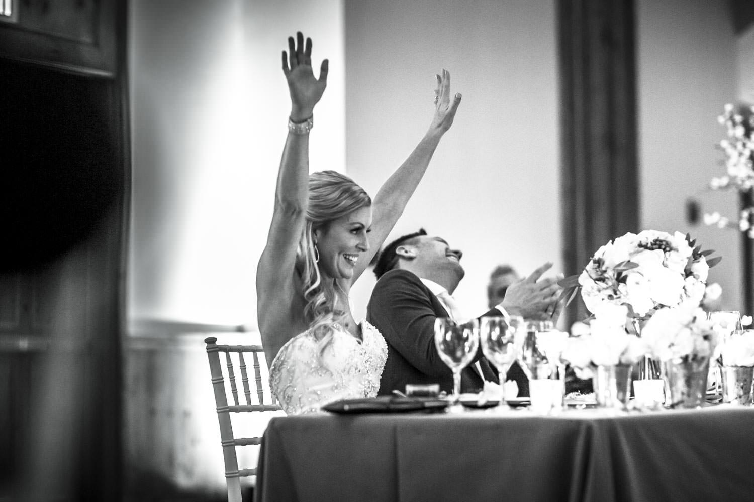 bride with hands up in celebration at conclusion of best man's wedding speech