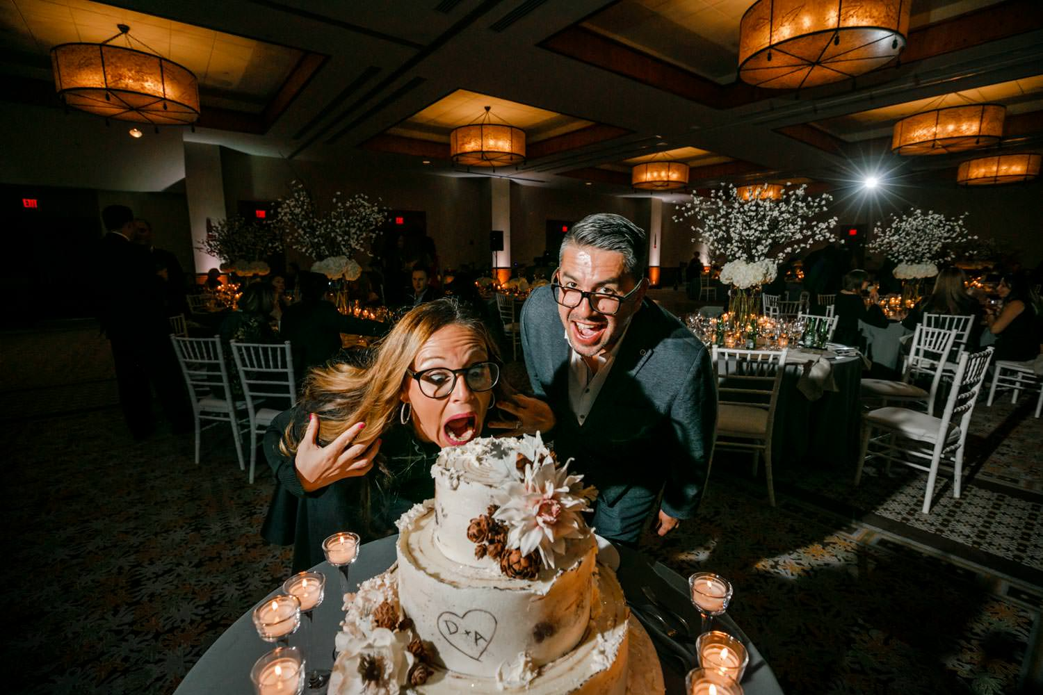 guests acting silly pretending to take a bite out of a wedding cake