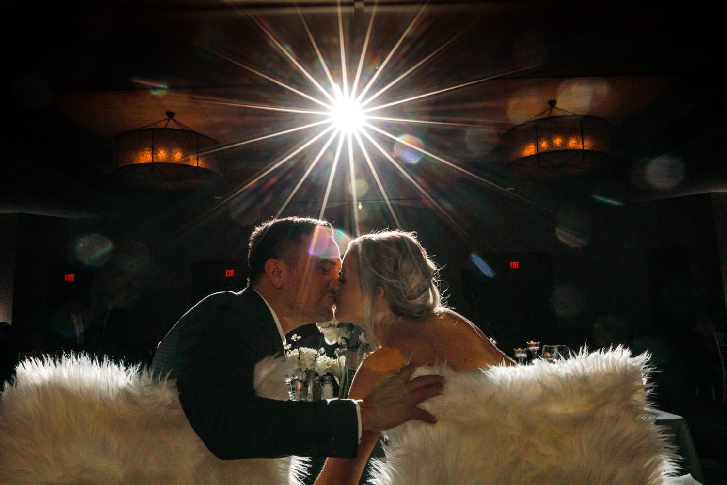 bride and groom kiss while sitting in chairs with a large starburst from photographer flash overhead