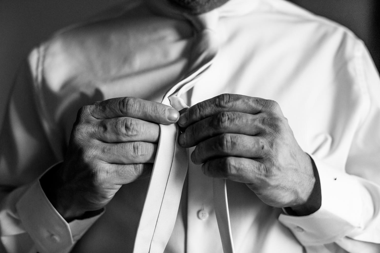 wedding photographer stowe vt captures groom buttoning up shirt