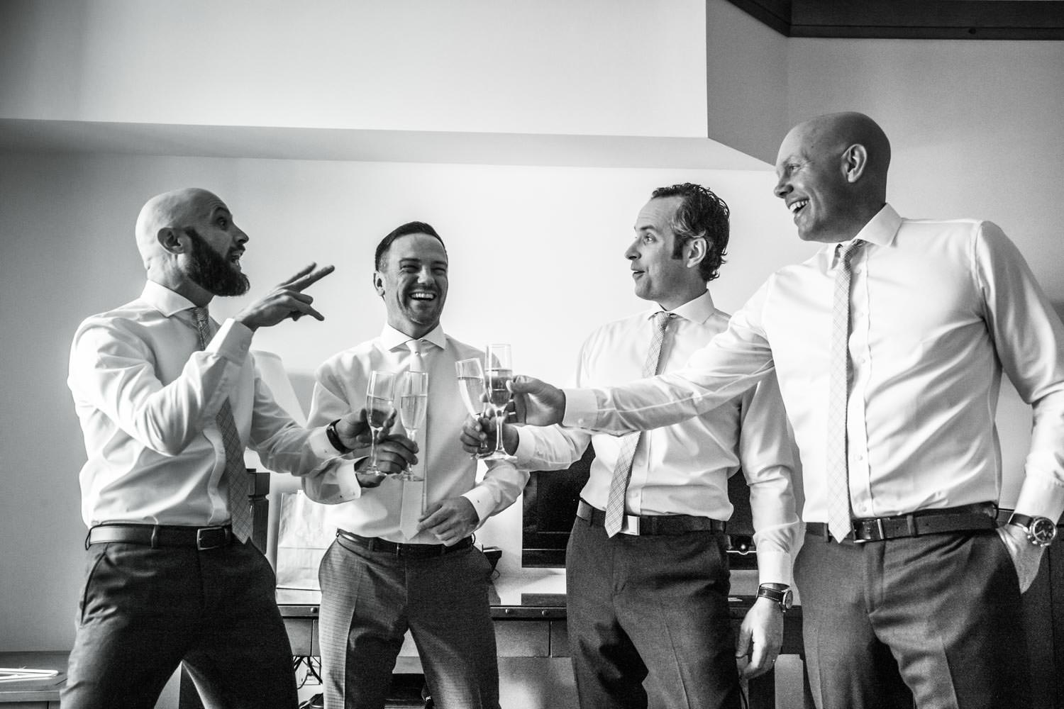 groomsmen toast champagne for stowe mountain lodge wedding photographer before vermont winter ceremony