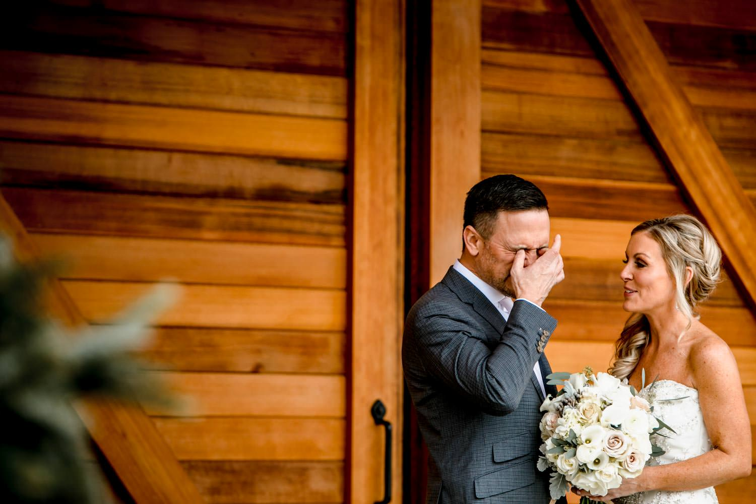 groom wipes away tears during first look before wedding ceremony in stowe mountain lodge vt