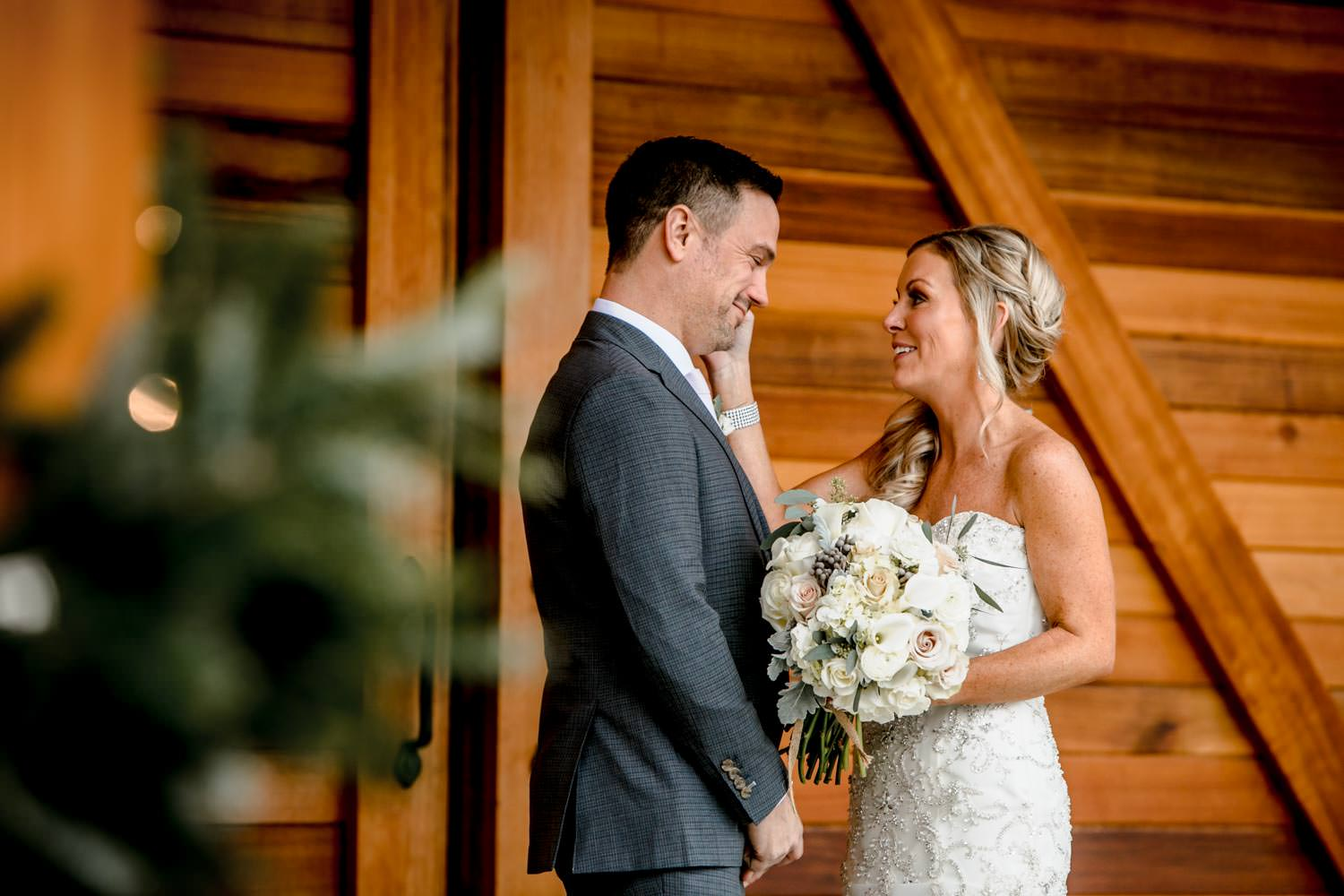 bride caresses grooms face during first look before ceremony at stowe mountain lodge mermont