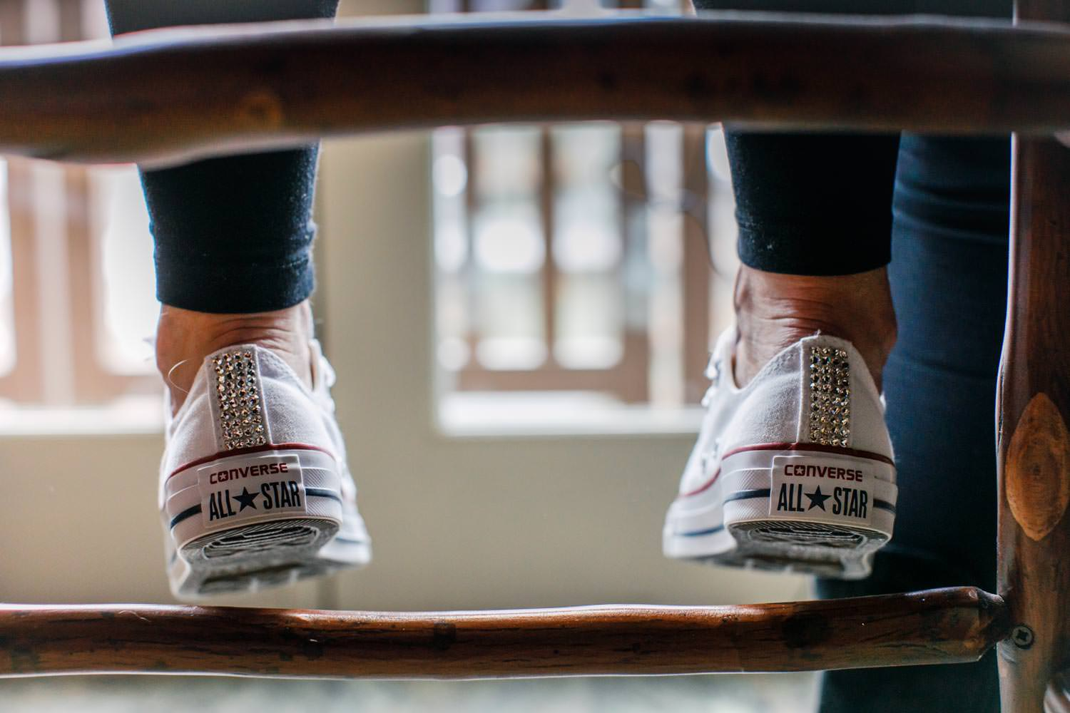bride's fun wedding sneakers captured from back while she sits in chair at Stowe Mountain Lodge