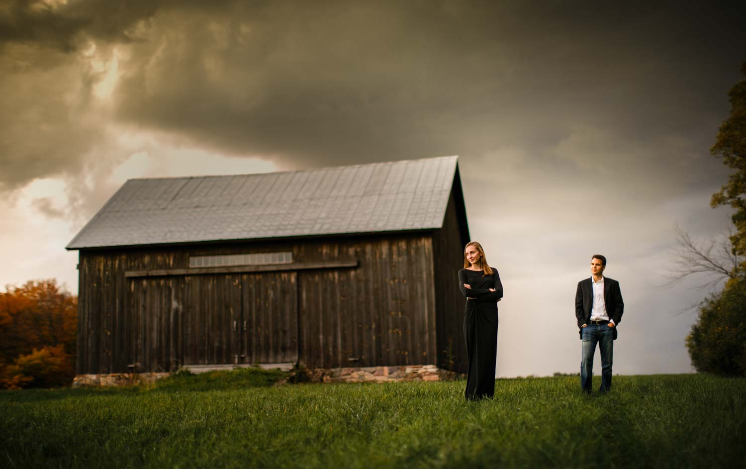 Engaged couple during Vermont wedding photographer engagement photo stands in front of barn in Shelburne