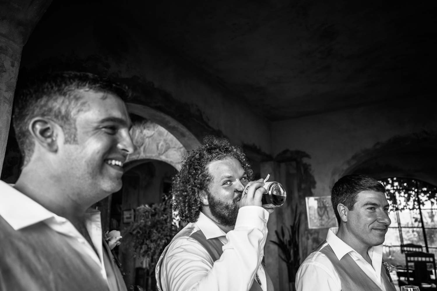 Best man drinks from bottle right before a wedding ceremony at Castle Club in Cabarete Dominican Republic