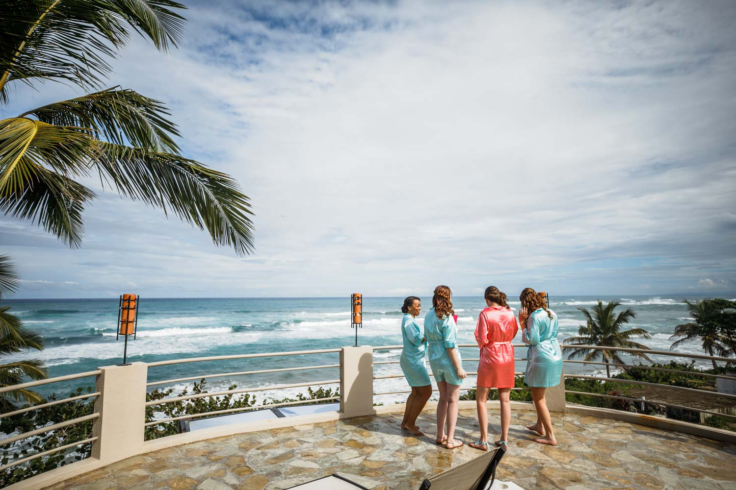Bridesmaids looking at ocean with photographer from the roof deck of wedding suite at Hotel Magnifico Cabarete Dominican Republic