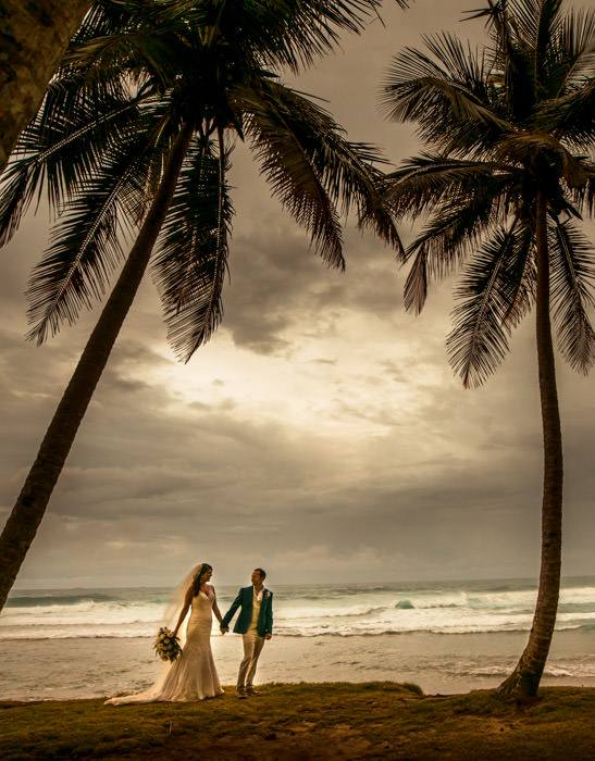 Bride and groom by the beach with palm trees at their wedding reception at Hideaway Beach Resort in Cabarete Dominican Republic