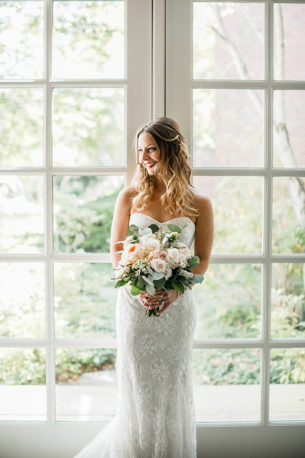 bride poses for vermont wedding photographer in front of windows at the woodstock inn