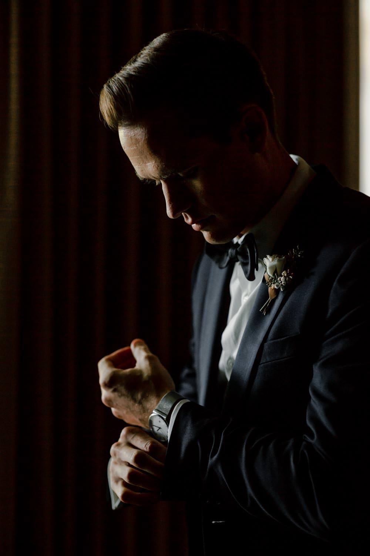 woodstock inn wedding groom adjusts cuff links for photographer to capture
