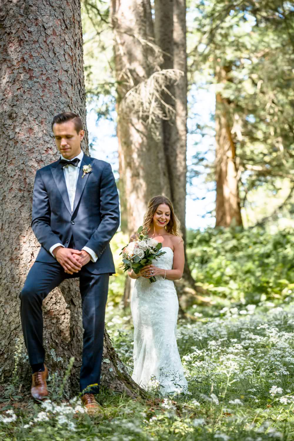 bride approaches groom who stands behind tree for first look photograph before their wedding