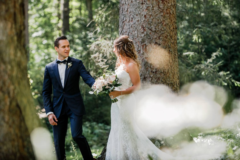 groom sees bride for first look before wedding in the woods at woodstock inn