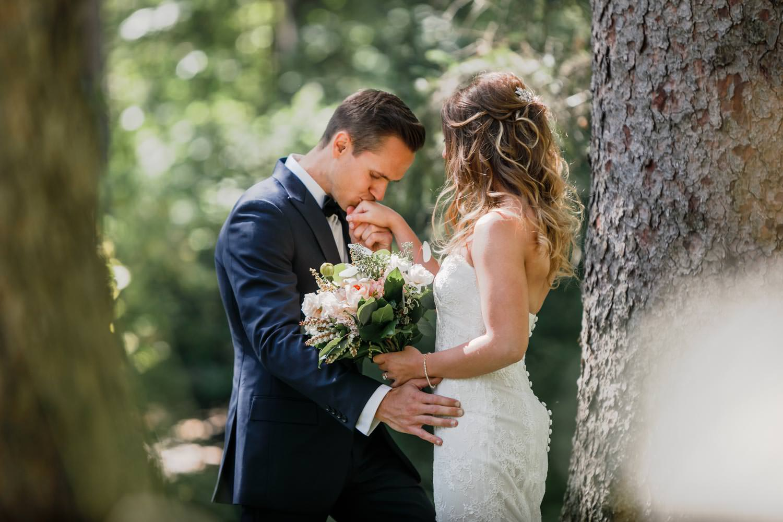 groom kissing bride's hand in the woodstock inn woods