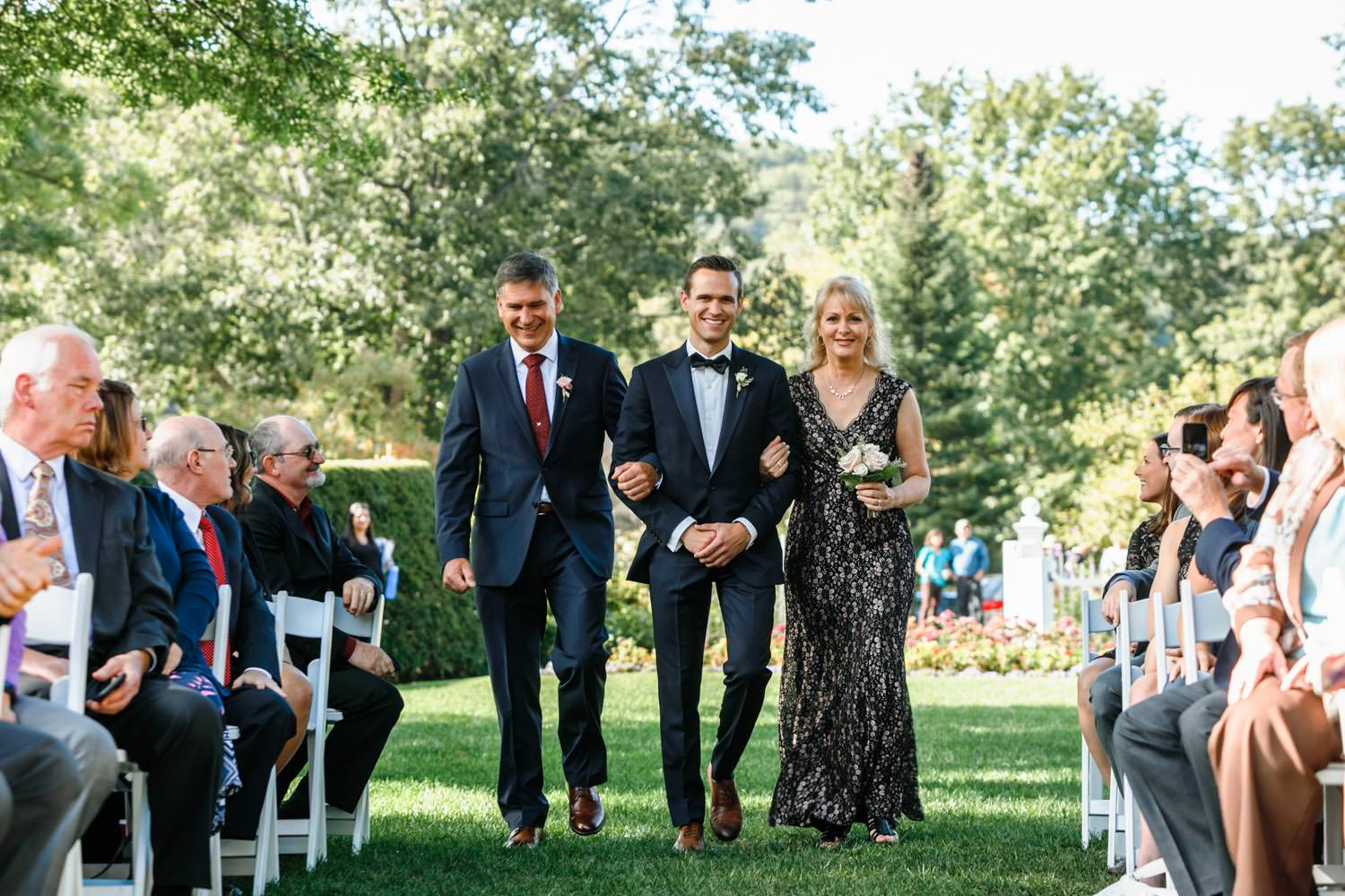 groom is walked down the aisle with mother and father for his wedding ceremony on the front lawn of the woodstock inn